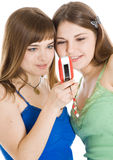 Due ragazze graziose che leggono SMS sul telefono mobile Fotografia Stock Libera da Diritti