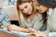 Due ragazze graziose che studiano nella conferenza corridoio Immagini Stock