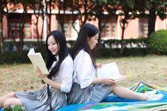Due ragazze graziose cinesi asiatiche adorabili il vestito dello studente che di usura nei migliori amici della scuola sorride li Fotografia Stock