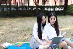 Due ragazze graziose cinesi asiatiche adorabili il vestito dello studente che di usura nei migliori amici della scuola sorride li Immagine Stock Libera da Diritti