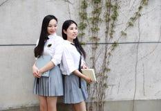 Due ragazze graziose cinesi asiatiche adorabili il vestito dello studente che di usura nei migliori amici della scuola sorride li Fotografia Stock Libera da Diritti