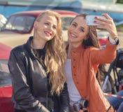 Due ragazze graziose dei pantaloni a vita bassa che prendono selfie Fotografia Stock Libera da Diritti