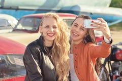 Due ragazze graziose dei pantaloni a vita bassa che prendono selfie Immagine Stock
