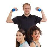 Due ragazze graziose ed uomo di forma fisica con i pesi Fotografie Stock Libere da Diritti