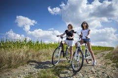 Due ragazze graziose sulle bici Fotografie Stock Libere da Diritti