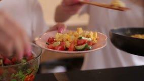 Due ragazze impongono un'insalata in un piatto, primo piano della verdura e dell'omelette archivi video