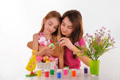 Due ragazze - le sorelle hanno dipinto le uova di Pasqua. su fondo bianco Fotografia Stock