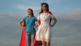 due ragazze in mantelli rossi dei supereroi stanno contro un cielo blu, il vento gonfia un mantello Gioco della figlia e della ma stock footage
