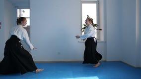 Due ragazze negli aikidi neri di pratica di hakama stock footage
