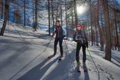 Due ragazze nel legno con gli sci di alpinismo salgono a Immagine Stock
