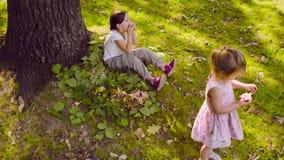 Due ragazze nel parco che mangiano granato video d archivio