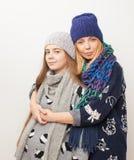 Due ragazze nell'inverno copre abbracciare sul fondo bianco Immagine Stock