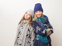 Due ragazze nell'inverno copre la risata sul fondo bianco Immagini Stock
