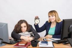 Due ragazze nell'ufficio a fine giornata, uno con un sorriso, tenente un orologio, le altre bugie stancate sulle cartelle Immagine Stock