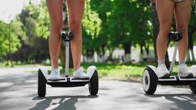 Due ragazze in pantaloncini corti guidano la macchina fotografica e sorridono al motorino di equilibrio nel parco archivi video