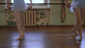 Due ragazze in scarpe di balletto fanno gli esercizi durante la classe di balletto in aula sfilacciata stock footage