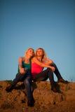 Due ragazze si siedono abbracciare e ridere del cielo blu Fotografie Stock Libere da Diritti