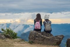 Due ragazze si siedono su una roccia che si esamina, il cielo blu con le nuvole e vista degli alberi verdi la bella da sopra il p immagine stock
