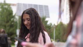 Due ragazze si siedono in un parco vicino ad una fontana facendo uso di uno smartphone e di una compressa in tempo soleggiato Mov archivi video