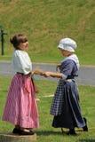 Due ragazze si sono vestite in abbigliamento di periodo durante la rievocazione della guerra di indiano e francese, Ontario forte Fotografia Stock Libera da Diritti