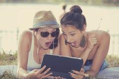 Due ragazze sorprese che esaminano cuscinetto che discute le ultime notizie del gossip Fotografia Stock