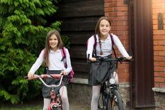 Due ragazze sorridenti che lasciano alla scuola sulle biciclette Immagini Stock
