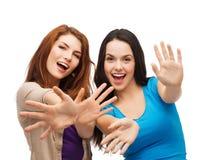 Due ragazze sorridenti che mostrano le loro palme Fotografia Stock