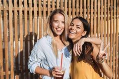 Due ragazze sorridenti che ridono mentre stando all'aperto fotografie stock libere da diritti