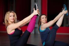 Due ragazze sorridenti fanno l'allungamento degli esercizi nel centro di forma fisica Immagine Stock Libera da Diritti