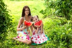 Due ragazze sorridenti mangia la fetta di anguria all'aperto sull'azienda agricola immagini stock libere da diritti
