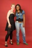 Due ragazze sorridenti su colore rosso Fotografia Stock Libera da Diritti