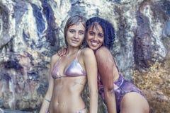 Due ragazze splendide si giocano sotto una piccola cascata Immagini Stock Libere da Diritti
