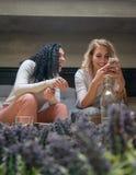 Due ragazze stanno esaminando il telefono e stanno sorridendo in caffè fotografia stock