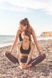 Due ragazze stanno facendo l'allungamento sulla spiaggia Fotografia Stock Libera da Diritti