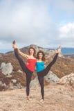 Due ragazze stanno facendo l'yoga nel paesaggio delle montagne Fotografia Stock Libera da Diritti