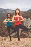 Due ragazze stanno facendo l'yoga nel paesaggio delle montagne Fotografie Stock Libere da Diritti