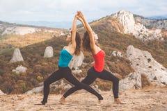 Due ragazze stanno facendo l'yoga nel paesaggio delle montagne Fotografia Stock