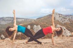 Due ragazze stanno facendo l'yoga nel paesaggio delle montagne Immagine Stock Libera da Diritti