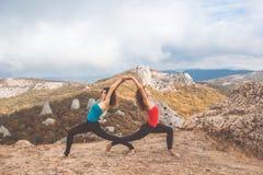 Due ragazze stanno facendo l'yoga nel paesaggio delle montagne Immagine Stock