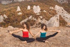 Due ragazze stanno facendo l'yoga nel paesaggio delle montagne Immagini Stock Libere da Diritti