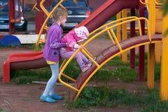 Due ragazze stanno giocando sul campo da giuoco Immagine Stock Libera da Diritti