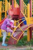 Due ragazze stanno giocando sul campo da giuoco Fotografia Stock