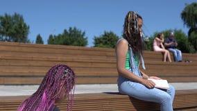 Due ragazze stanno leggendo un libro che si siede su un banco di legno nel parco Movimento lento archivi video