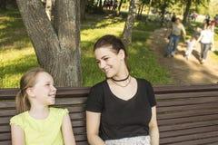 Due ragazze stanno sedendo su un banco che parlano e che ridono Fotografia Stock Libera da Diritti