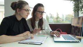 Due ragazze stanno sedendo in un caffè, facendo uso di un computer portatile e stanno discutendo le idee di affari video d archivio