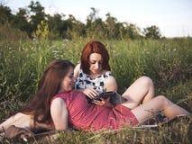 Due ragazze su un resto all'aperto immagine stock libera da diritti