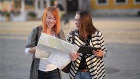 Due ragazze sulle vie di vecchia città Le amiche provano a trovare il loro modo in una città poco familiare Ragazza Red-haired archivi video