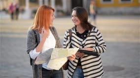 Due ragazze sulle vie di vecchia città Le amiche provano a trovare il loro modo in una città poco familiare turisti stock footage