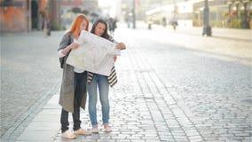Due ragazze sulle vie di vecchia città Le amiche provano a trovare il loro modo in una città poco familiare turisti video d archivio
