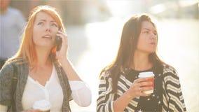 Due ragazze sveglie sono alla via nella città Le ragazze stanno tenendo le tazze di carta con caffè La ragazza Redheaded parla su video d archivio